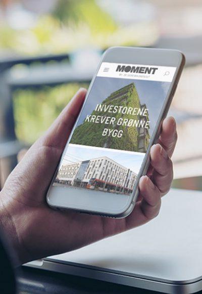 Hånd holder mobil som viser Sweco Moment. Uskarp bakgrunn med laptop og vindu