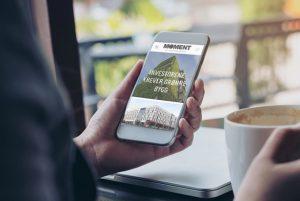 Hånd i kafémiljø holder mobil som viser Sweco Moment. Uskarp bakgrunn med hånd som holder kaffekopp, laptop og vindu
