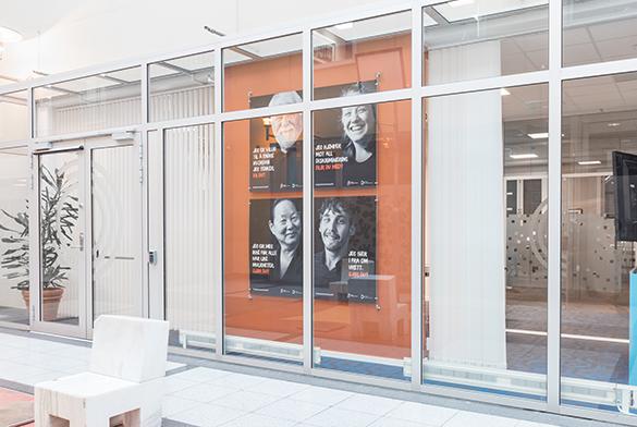 Vindusflate hvor portretter med tekst er montert på en stor orange flate.